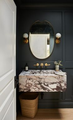Moody modern powder room interior design with floating vanity and wall mounted brass faucet #powderroomdesign