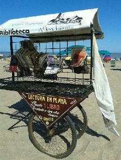 "Original pinner: ""bookmobile"" -- SH: Wish I could read the words a bit more clearly in this photo, but I can read that it's ""Reading on the Beach"" and that people are invited to take one book and that the books are free. Can't tell what the ""Aldea"" (or Village) is..."