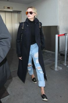 Margot Robbie defined understated chic in distressed denim and a structured black coat at LAX.