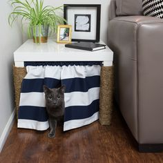 Litter boxes aren't typically design elements in home decor. This smart and stylish solution, however, hides the box in plain sight — and looks great, too! 1. Gather a basic side table, some twisted jute rope, a short tension rod, and two window valances.  2. Wrap the rope around the table's front legs to cover them and create a DIY scratching post.  3. Put the valances on the tension rod and secure it at the top of the table's legs.  4. Slide your kitty's litter box into the space under…