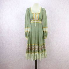 Vintage 70s Gunne Sax Prairie Midi Dress. Sage green floral pattern with white floral pattern color blocking. Empire waist with lace up bust and lace trim. Gold ribbon trim throughout with back zipper