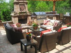 Rattan outdoor furniture is positioned around a focal fireplace, creating an intimate sitting area. A stainless steel grill sits nearby for convenient cooking. Pops of red in the pillows and flowers add character to the space.