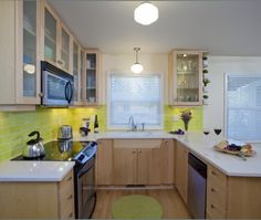The bright lime green subway tile backsplash  accent in this transitional U-shaped kitchen with maple cabinets creates a wonderful modern feel.