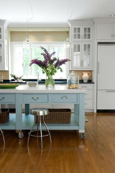 Industrial backless nickel stools sit in front of a blue freestanding island finished with a shelf holding wicker baskets, drawers adorning polished nickel pulls, and a  honed white marble countertop illuminated by three glass light pendants.