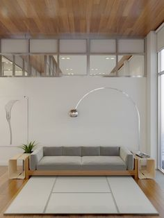 The living room and kitchen are open to one another and both utilize a white, gray, and natural wood look.