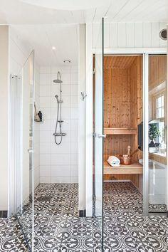 kleines Bad mit ornamentalem Boden, Duschkabine mit Regendusche, Sauna Kabine mit Fenster, Decke mit Holzverkleidung