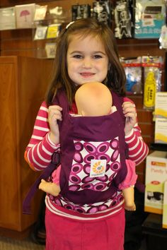 """Snugglebugz: This is a great gift idea for any young girl who loves her """"babies"""".  Children can mirror other """"moms"""" with the child-sized Ergobaby Doll Carrier.  It is perfect for toting beloved dolls and other toy friends and is a great gift for a new big sister or brother, so they can be just like mommy or daddy.  The Doll Carrier can be worn in the front or back position and we had a perfect product tester join us and she seemed pretty happy to have her favourite dolly in tow."""