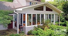Traditional sunroom with glass wings under a shingled gable roof. #homeimprovement #sunrooms