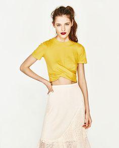 CAMISETA FRUNCE BAJO de Zara    Camiseta con largo por la cintura. Cuello redondo. Manga corta. Frunce en bajo delantero. Tejido elástico.