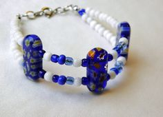 Double strands of glass beads connect oblong glass beads with floral patterns. $8