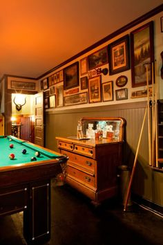Wainscoting makes this space feel very much like a gaming room. It also helps to focus the eye up toward the framed memorabilia.