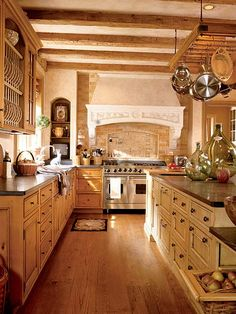 Earth tones prevail in this open kitchen that looks as if it's been in place for centuries. Open shelving, naturally finished cabinets, and a pot rack over the center island provide abundant storage. Accessories personalize the space, and the tile backsplash over the stove makes the kitchen feel even more unique. (Photo: Photo: Gordon Beall; Designer: Barry Dixon)
