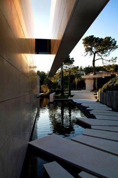 Wunderschöne, großformatige Trittsteine überqueren Gartenteich an Designer-Haus