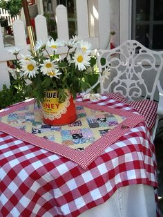 Love the old can with flowers planted and the table cloth on the table.