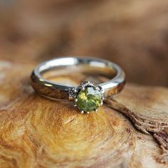 Associated with beauty and purity, the lotus flower is the perfect symbol of your blooming love. This peridot engagement ring is fashioned in 10k white gold with an organic black ash burl inlay. The magical lotus setting is decorated with sparkling diamonds for an extra flash of beauty.  This wood engagement ring comes with FREE ring armor waterproofing (a $75 value).  RING PRICED FOR THESE SPECIFICATIONS Ring Size: 7 Ring Width: 3.5 mm Ring Sleeve: 10k White Gold Ring Profile: Round Ring…