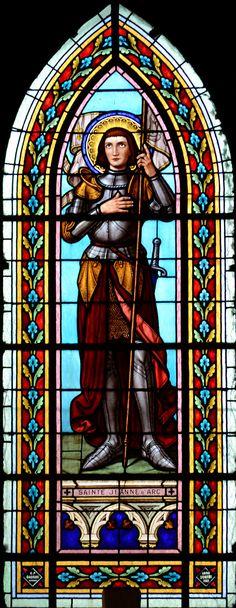 Sainte Jeanne d'Arc. Chef de guerre, elle est vêtue d'une armure des pieds jusqu'au cou, tient un étendard blanc frappé de la fleur de lys, et une épée est accrochée à son côté gauche. Pieuse, la main droite sur sa poitrine, elle lève les yeux au ciel.