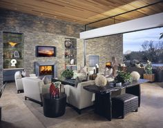 Ultra modern take on the living room, using classical materials. Stone brick wall extends through to the exterior, while tile flooring continues seamlessly through wide opening to patio space. Grey and black furniture adds subtle contrast.