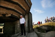An Italian tourist views a bunker at a strategic site overlooking the D-Day beaches which had been captured by US Army Rangers at Pointe du Hoc, France