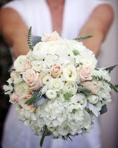 Romantic and garden-y bridal bouquet of white hydrangea, roses, ranunculus and veronica mixed with pale pink roses and dusty miller.
