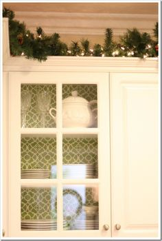 Christmas lights above kitchen cabinets with faux garland
