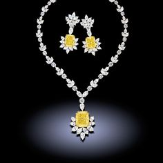 A 54.29 ct. Fancy Intense yellow diamond suspended from a necklace set with 67.10 carats of colorless diamonds and earrings by Chatila