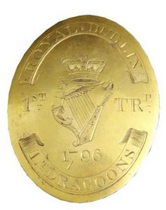FIRST TROOP, ROYAL DUBLIN LIGHT DRAGOONS, LATE 18TH C IRISH YEOMANRY SHOULDER BELT PLATE.   Oval, gilt on copper, crowned Maid of Erin harp engraved at centre dividing the designation ''1st'' and ''TRp'', the date ''1796'' engraved in the field below, twin ribbons above and below bearing the regimental title ''Royal Dublin Lt. Dragoons'', twin hooks and pair of fixing studs to reverse, circa 1796, 3.25'' x 2.5'' (8.3 x 6.4cm) vertical approx.