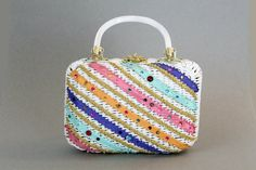 This vintage handbag is great for summer! Its got so many fantastic and fun colors! Stripes of aqua, blue, orange and pink are divided up by