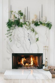 Marble fireplace with vines and foraged foliage and Mexican onyx hurricanes.
