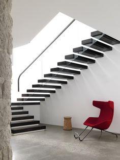 modern staircase, white walls, railing, egg chair, cement floor