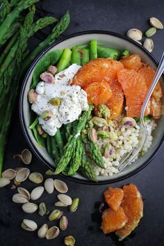 A warm, healthy spring bowl of Israeli couscous with asparagus, lemon butter, goat cheese, Cara Cara oranges, and pistachios.