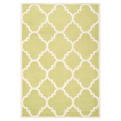 Gold and ivory wool rug with a quatrefoil trellis motif. Hand-tufted in India.   Product: RugConstruction Material: