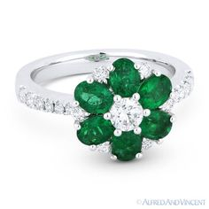 The featured flower-design ring is cast in 18k white gold and showcases oval cut emerald petals & round cut diamond accents paved on the flower design and on both sides of the ring's band.