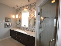 This contemporary bathroom is a study in geometry. Round mirrors and sinks are juxtaposed with an oblong window, horizontal backsplash tiles in a random pattern, a rectangular glass shower door, and a linear vanity with flat-panel cabinets.