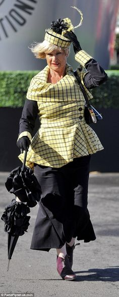 One woman opted for an elegant covered-up look as she arrived at the course - and even brought an umbrella for good measure