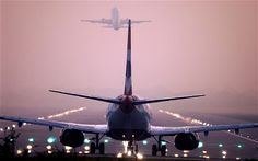 Rear view as two jet planes follow each other almost nose to tail on take off from London Gatwick airport