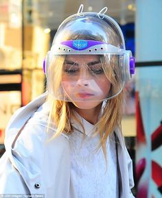 What a stylish space ranger! Cara Delevingne teams odd helmet with cute white sheer dress and trainers on DKNY set in New York