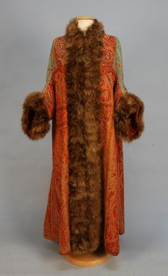 Early 20th c. MARABOU TRIMMED WOOL PAISLEY EVENING COAT. Fashioned from a Kashmiri shawl, three quarter sleeve, having feathers decorating the neckline, front, sleeves and back vent with self buttons, lined in red silk with inside tie, front hook & eye closures. B-38, L-52.