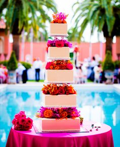 Multi-tiered square cakes and bright flowers for a tropical wedding