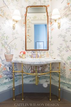 Whimsical angled powder room is clad in de Gournay Ardinières Citrus Trees Wallpaper lined with gray baseboards and boasts a brass based marble washstand fitted with an oval sink and brass vintage faucet kit positioned beneath a wood and gold framed vanity mirror lit by Ginger Single Arm Sconces.