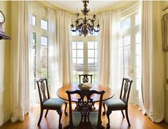 Design by Thomas Jayne:  The breakfast room is encircled by French doors framing an idyllic view of the country side. Curtains and sheer panels are hung from a double set of brass rods following the curve of the architecture.