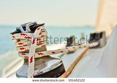 stock photo : Red and white line wrapped around winch of sailboat