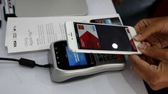 A worker demonstrates Apple Pay inside a mobile kiosk sponsored by Visa and Wells Fargo to demonstrate the new Apple Pay mobile payment system on October 20, 2014 in San Francisco City