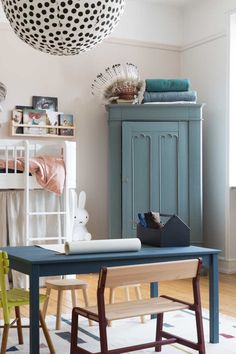 A Loft bed with curtains and blue vintage wardrobe in an adorable children's bedroom in Southern Sweden