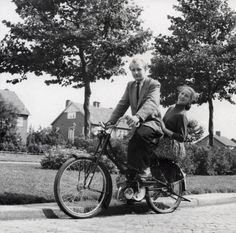 Bromfietsen/snorfietsen Nederland. Een tochtje op de bromfiets ( onbekend merk). Dame zit op de bagagedrager. 1953, ergens in Nederland..