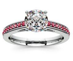 Twenty four round cut ruby gemstones are pave set in this white gold gemstone engagement ring setting, accenting your choice of center diamond.