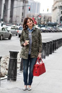 camo jacket + red handbag + skinny jeans + graphic tee
