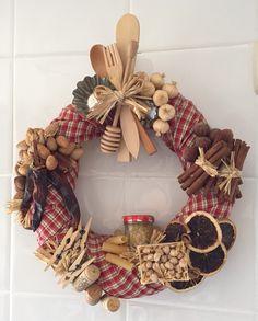 Corona para cocina. Materiales; corona de paja, tela estampada, frutos secos, corchos, cubiertos de madera, ñoras, pinzas de madera, etc., todo pegado con pegamento caliente.
