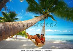 stock photo : view of nice woman reading a book in hammock in tropical environment