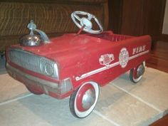 Pedal car fire truck. We totally had one exactly like this, even though by the time we were kids it was already an old toy.  It was a respected part of our fleet of child vehicles.