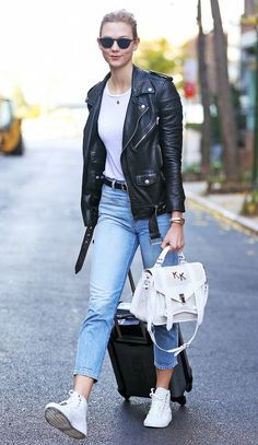 Karlie Kloss wears a Saint Laurent moto jacket with a plain white tee, cropped skinny jeans, a white top handle bag, and white high top sneakers